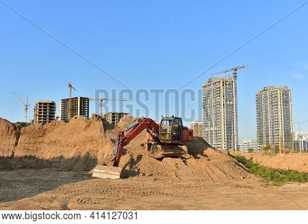 Bucket Wheel Excavator On Earthmoving At Construction Site. Backhoe Digs Sand On Blue Sky Background