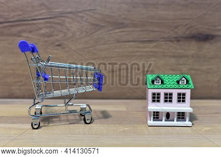 House And Supermarket Trolley. Home Buying Or Selling. Building On Credit Housing Or Renting An Apar