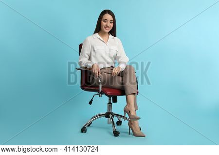 Young Businesswoman Sitting In Comfortable Office Chair On Turquoise Background
