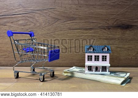 House In Supermarket Trolley And American Dollars. Home Buying Or Selling. Building On Credit Housin