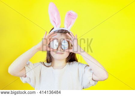 Easter Concept. Portrait Of A Cute Girl With Bunny Ears Dabbles With Painted Eggs, Covers Her Face O