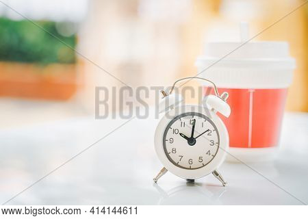 White Analog Clock At Ten O'clock And Blurred Plastic Hot Coffee Cup On Desk For Coffee Break With C