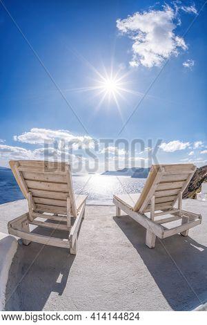 Relaxation On Sunbeds Against Sunset In Oia Village, Santorini Island, Greece