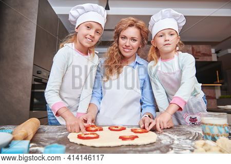 Happy mother and her daughters cook pizza in the kitchen at home. Happy family. Healthy food at home.