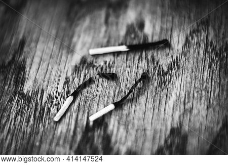 A Black-and-white Image Of Three Burnt Matches Lying On A Wooden Table. One Of The Matches Burned Ou
