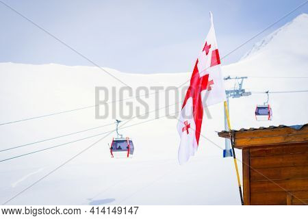Georgian Flag With Gudauri Panorama And Ski Cabin Lifts And Snowy Mountain Background.ski Holiday De