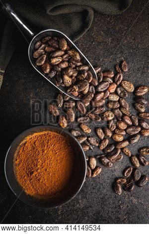 Cocoa powder and cocoa beans in scoop on black table. Top view.
