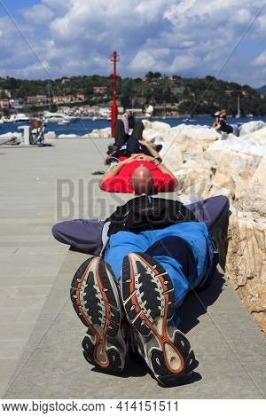 Portovenere (sp), Italy - April 15, 2017: Tourist Relaxing On A Wall In Portovenere, Gulf Of Poets,
