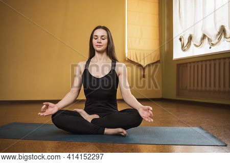 Young Attractive Woman In Black Sportswear, Practicing Yoga, Is Engaged In Meditation In The Lotus P