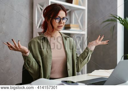 Young confused mid aged woman entrepreneur working on laptop computer in office, shrugging shoulders