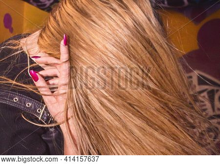 Brown-haired Girl Throws Hair In Dance Close-up With Hand With Purple Manicure.