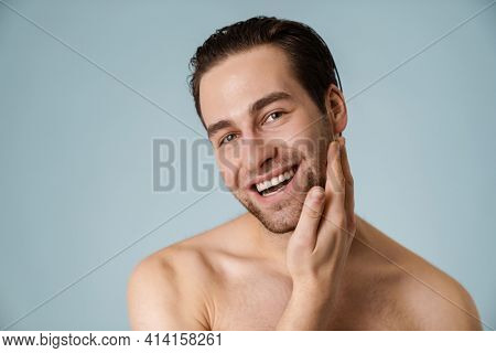Close up of a smiling brunette shirtless man with stubble over blue background, touching face