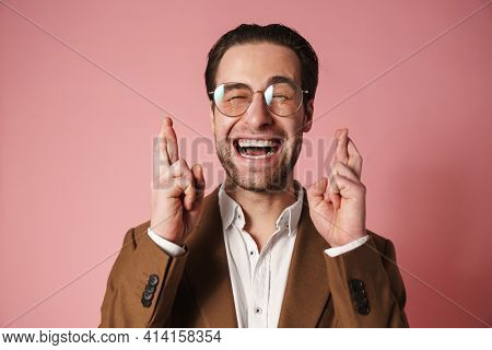Happy young brunette man in jacket holding fingers crossed for good luck over pink wall