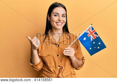Young brunette woman holding australian flag pointing thumb up to the side smiling happy with open mouth