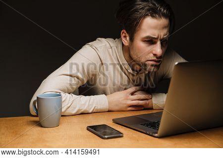 Serious pensive brunette businessman working on laptop computer in dark office