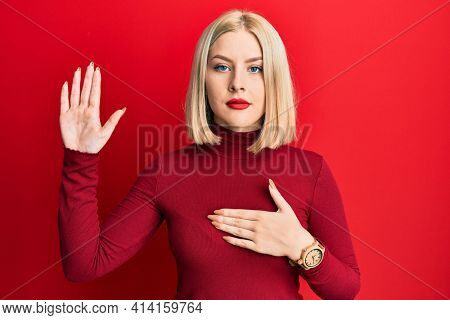 Young blonde woman wearing casual clothes swearing with hand on chest and open palm, making a loyalty promise oath