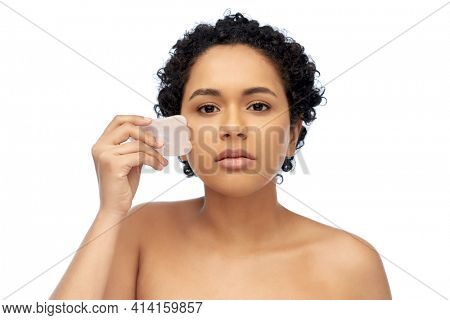 young woman massaging her face with gua sha tool