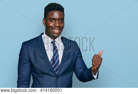 Handsome business black man wearing business suit and tie smiling with happy face looking and pointing to the side with thumb up.