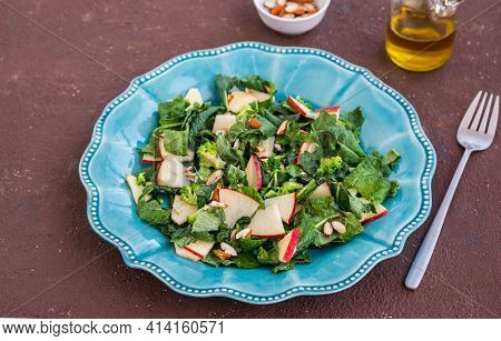 Healthy Salad With Kale, Apple And Almonds In A Blue Plate On A Brown Concrete Background. Kale Reci