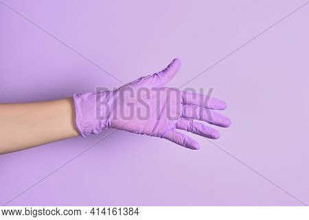 A Woman's Hand In A Medical Rubber Lilac Glove Reaches Out To Shake On An Isolated Purple Background