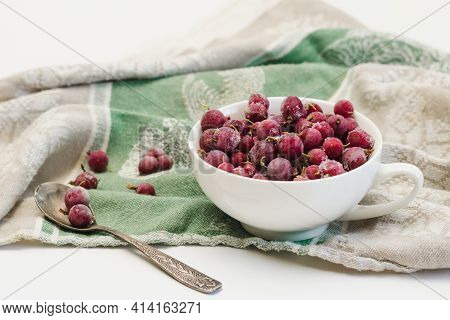 Frozen Berries Of Red Gooseberries With Hoarfrost In A White Cup And A Spoon On An Old Linen Tablecl