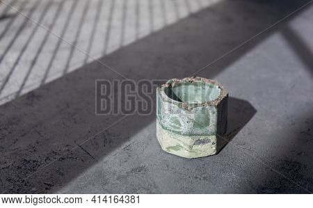 Empty Green Stone Candle Holder With Abstract Smudges, Cracks On Gray Concrete. Sunny Shadows And Si