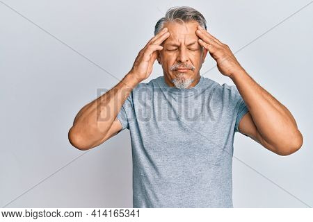 Middle age grey-haired man wearing casual clothes with hand on head, headache because stress. suffering migraine.