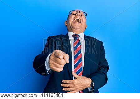 Senior caucasian man wearing business suit and tie laughing at you, pointing finger to the camera with hand over body, shame expression