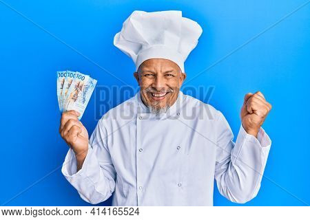 Middle age grey-haired man wearing professional cook uniform holding swiss franc banknotes screaming proud, celebrating victory and success very excited with raised arm