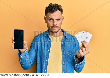 Young hispanic man holding poker cards and smartphone showing blank screen skeptic and nervous, frowning upset because of problem. negative person.