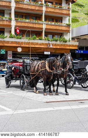 Zermatt, Switzerland - June 22, 2019: Horse-drawn Vehicle And Traditional Houses In The Centre Of Ze
