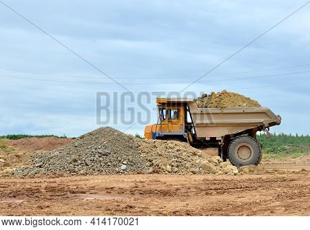 Mining Truck And Excavators Working In The Limestone Open-pit. Loading And Transportation Of Mineral