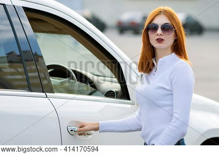 Yong Pretty Woman Standing Near A Big All Terrain Car Outdoors. Driver Girl In Casual Clothes Outsid