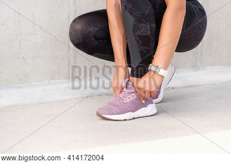 Close Up Shoot Of Woman's Hands Tying The Shoelaces Of Sporty Sneakers. Fitness Sporty Woman Is Prep