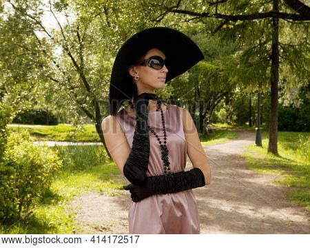 Posh woman in retro dress and big black hat posing in the park. Vintage style, fifties era.