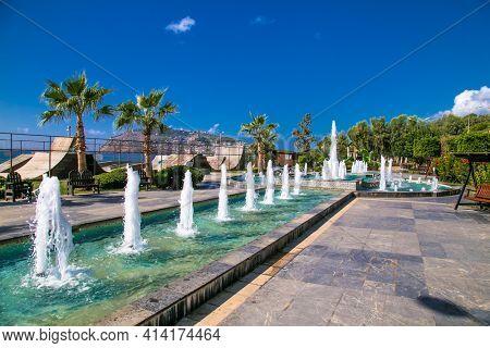 Turkey, Alanya - October 20, 2020: Beautiful Fountain on Alanya promenade - Ahmet Tokus Boulevard along all Beaches. Tourists promenade along the alley along the Mediterranean coast. Alanya, Turkey