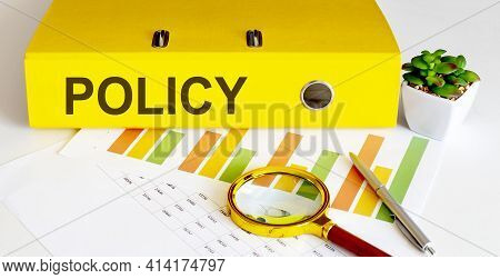 Office Folder With Text Policy On Charts, Magnifier And Pen