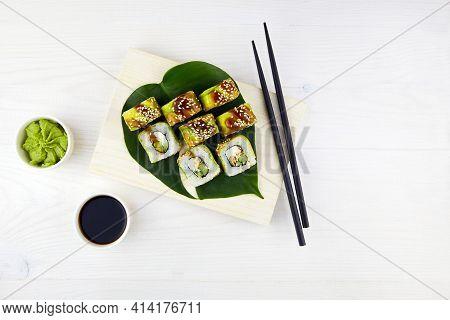 Sushi Set On Wooden Background. Sushi Roll Maki With Filling Of Cream Cheese, Smoked Eel, Cucumber,