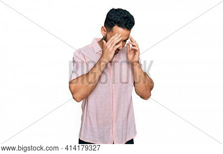 Hispanic man with beard wearing casual shirt with hand on head for pain in head because stress. suffering migraine.
