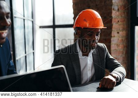 African American Man In Formal Suit Sits At A Table In A Construction Helmet Next To Another Worker
