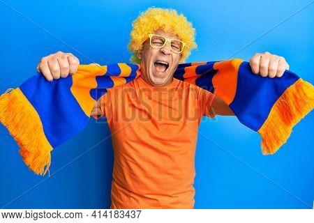 Senior hispanic man football hooligan cheering game smiling and laughing hard out loud because funny crazy joke.