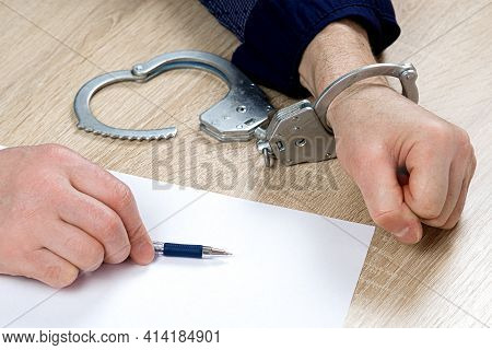 A Man Writes A Confession At The Police Station. One Hand Is Cuffed, The Other Is Unbuttoned, Pen In
