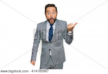 Middle age man wearing business clothes surprised pointing with hand finger to the side, open mouth amazed expression.