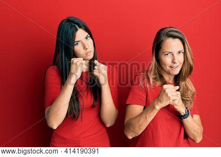 Hispanic family of mother and daughter wearing casual clothes over red background ready to fight with fist defense gesture, angry and upset face, afraid of problem