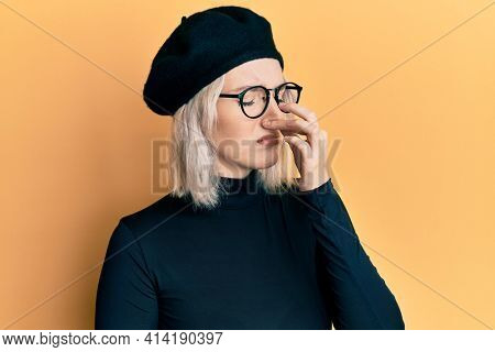 Young blonde girl wearing french look with beret smelling something stinky and disgusting, intolerable smell, holding breath with fingers on nose. bad smell