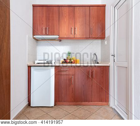 Front View Of Wooden Kitchen Cupboard Module Cabinet With Small Fridge And Fruits Plate, Classic Sty