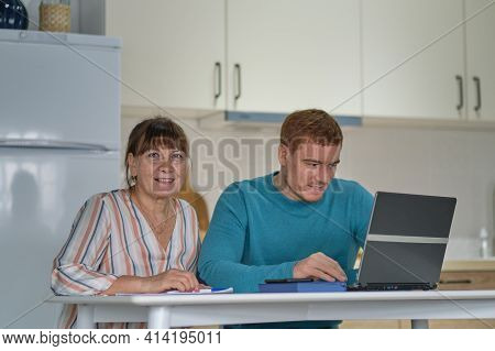 Man Teaching His Mother Shopping Online Using Laptop At Home. Older Woman And Young Man Using Laptop