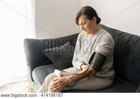 Senior Woman Checking Blood Pressure Level At Home, Older Female Suffering From High Blood Pressure