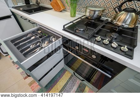 Drawers with silverware and other kitchen utensils pulled out with content in cabinet at luxury teal and white modern kitchen furniture, high angle view