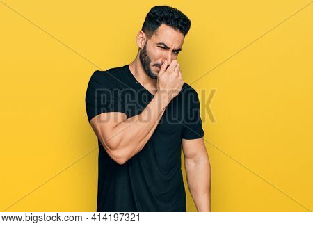 Hispanic man with beard wearing casual black t shirt smelling something stinky and disgusting, intolerable smell, holding breath with fingers on nose. bad smell